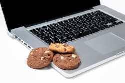 laptop with cookies lying on top